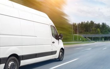 White modern delivery small shipment cargo courier van moving fast on motorway road to city urban suburb. Busines distribution and logistics express service. Mini bus driving on highway on sunny day